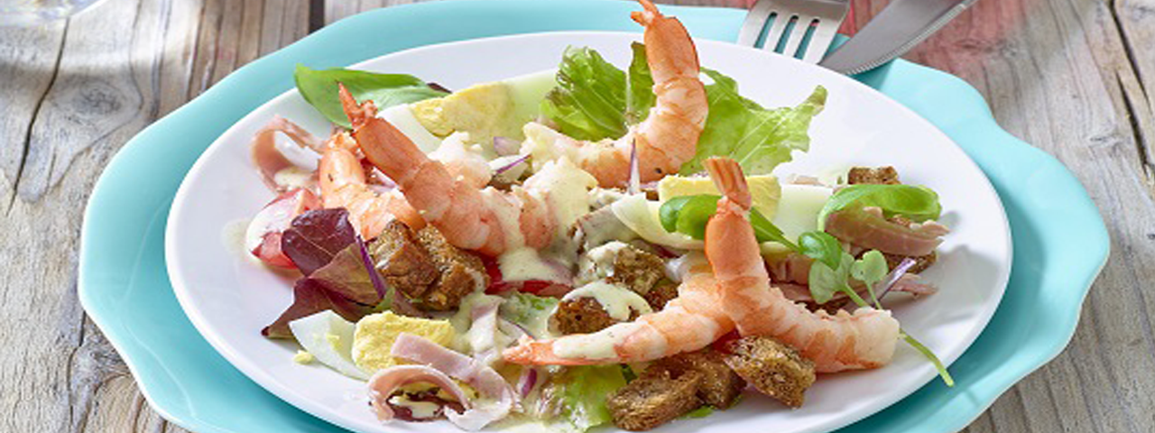 Shrimps salad with croutons and grilled ham