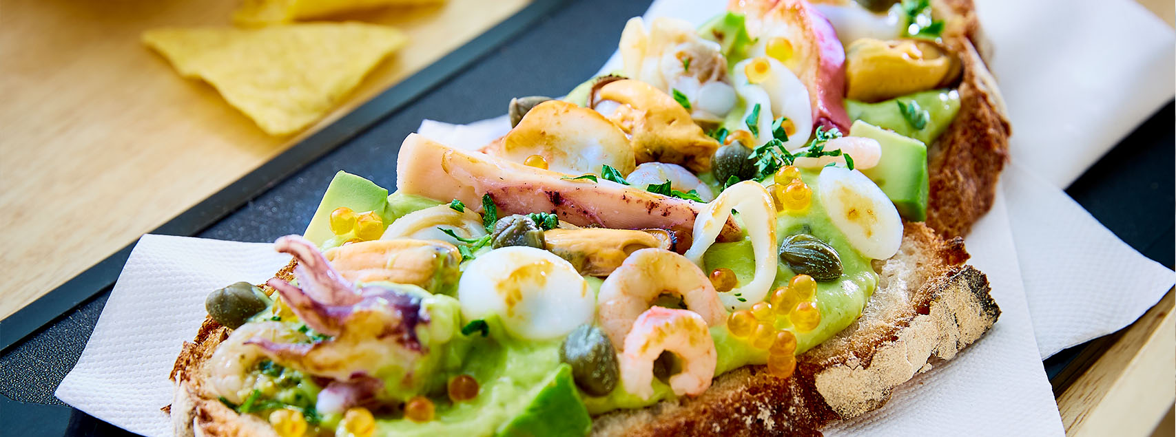Seafood toasts with guacamole and salmon eggs